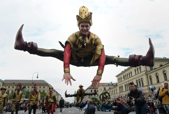 An impostor jumps during the traditional costume parade of the Bavarian Oktoberfest festival in in the city of Munich, southern Germany, on September 21, 2014. Germany's world-famous Oktoberfest kicks off with millions of revellers set to soak up the frothy atmosphere in a 16-day extravaganza of lederhosen, oompah music and beer. (Photo by Christof Stache/AFP Photo)