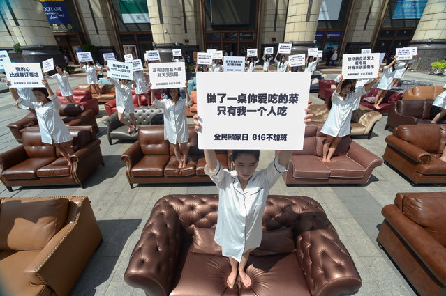 "Participants hold placards as they stand on sofa during a performance art to protest against husbands who overworked, in Shanghai, China, August 8, 2016. The Chinese characters on the placard (C) read, ""I had to eat alone when I made a table of your favorite dishes"". (Photo by Reuters/Stringer)"