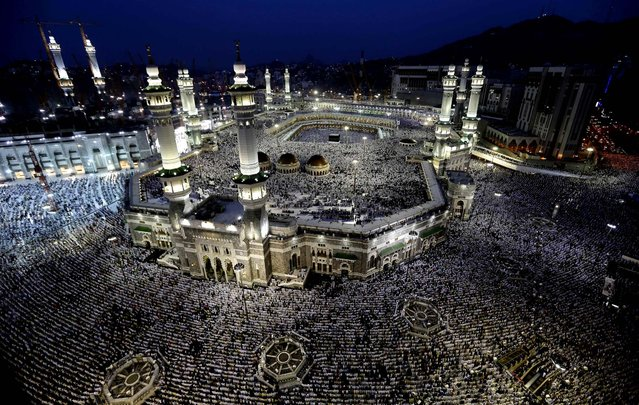 Muslim pilgrims circle the Kaaba as people pray inside and outside the Grand Mosque in Mecca, Saudi Arabia October 22, 2012. The annual Islamic pilgrimage draws two to three million visitors each year, making it the largest yearly gathering of people in the world. (Photo by Hassan Ammar/Associated Press)