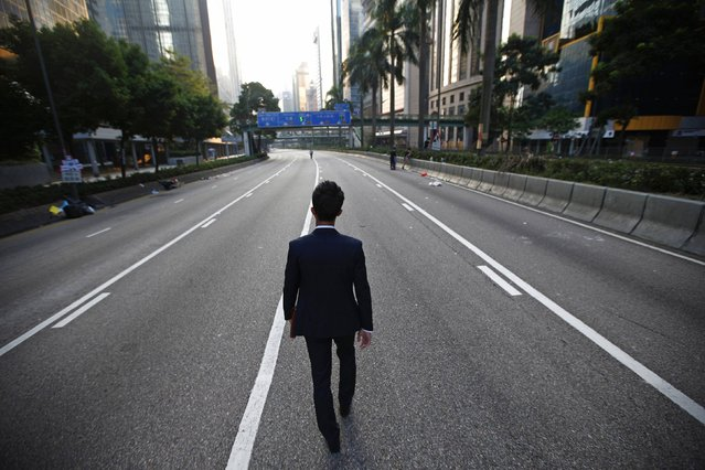 A man walks along an empty street near the central financial district in Hong Kong September 30, 2014. Tens of thousands of pro-democracy protesters extended a blockade of Hong Kong streets on Tuesday, stockpiling supplies and erecting makeshift barricades ahead of what some fear may be a push by police to clear the roads before Chinese National Day. (Photo by Carlos Barria/Reuters)