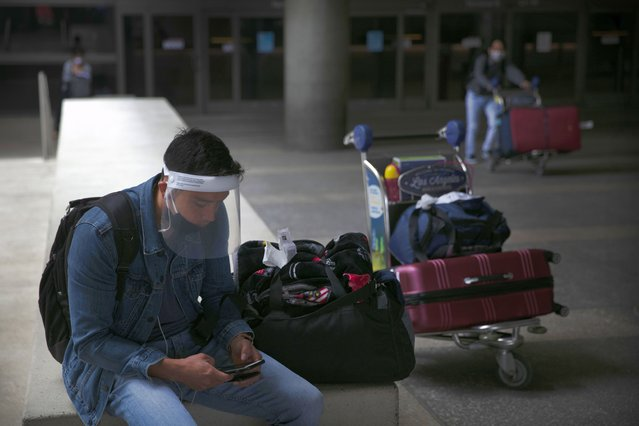 A traveler wearing a face shield looks at his phone outside the arrivals area at Los Angeles International Airport on Wednesday, June 24, 2020, in Los Angeles. The United States recorded a one-day total of 34,700 new COVID-19 cases, the highest in two months, according to the count kept by Johns Hopkins University. (Photo by Jae C. Hong/AP Photo)