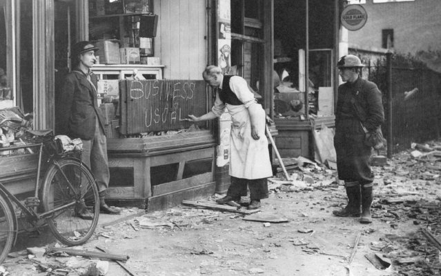 A London shopkeeper in the East End dock area puts up a business as usual sign, September 18, 1940 after his shop had been damaged by bombing. (Photo by AP Photo)