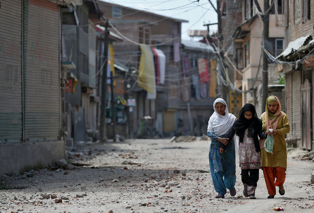 Two women and a girl make their way along a street littered with rocks thrown by protestors in Srinagar as the city remains under curfew following weeks of violence in Kashmir August 19, 2016. (Photo by Cathal McNaughton/Reuters)