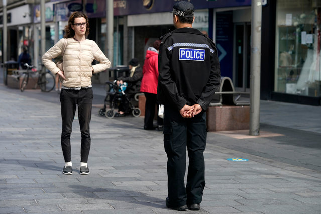A police officer keeps his social distance as he talks to a shopper in Leicester City Centre before non-essential shops close for the localised pandemic lockdown on June 30, 2020 in Leicester, England. As the rest of England prepares to reopen pubs and restaurants this weekend, Leicester is closing all non-essential businesses again after a spike in coronavirus cases worried officials. (Photo by Christopher Furlong/Getty Images)