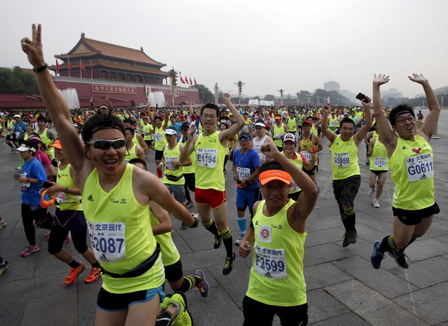 Participants jumps to pose to photographers as they run past the Tiananmen gate during the Beijing International Marathon in Beijing, China, September 20, 2015. (Photo by Kim Kyung-Hoon/Reuters)