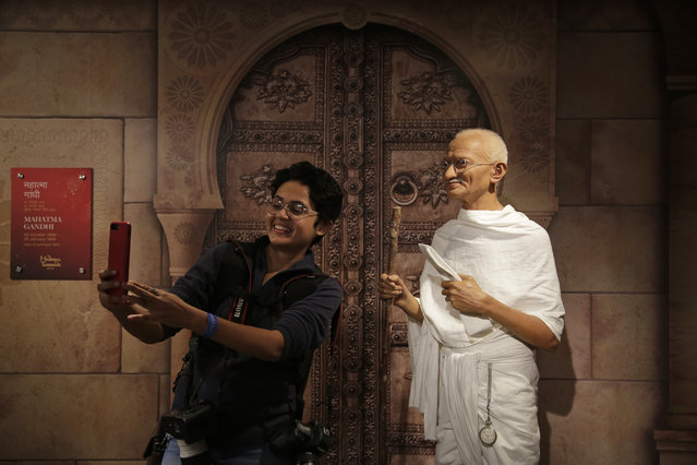 A news photographer takes a selfie with a wax figure of Mahatma Gandhi during apress preview of Madame Tussauds Wax Museum in New Delhi, India, Thursday, November 30, 2017. (Photo by Altaf Qadri/AP Photo)