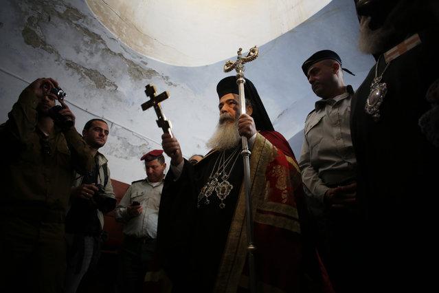 Greek Patriarch Metropolitan Theophilos holds a cross during a ceremony at the baptismal site known as Qasr el-Yahud on the banks of the Jordan River near the West Bank city of Jericho January 18, 2013. (Photo by Baz Ratner/Reuters)