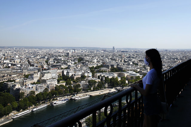 A visitor looks at the view from the Eiffel Tower, in Paris, Thursday, June 25, 2020. The Eiffel Tower reopens after the coronavirus pandemic led to the iconic Paris landmark's longest closure since World War II. (Photo by Thibault Camus/AP Photo)