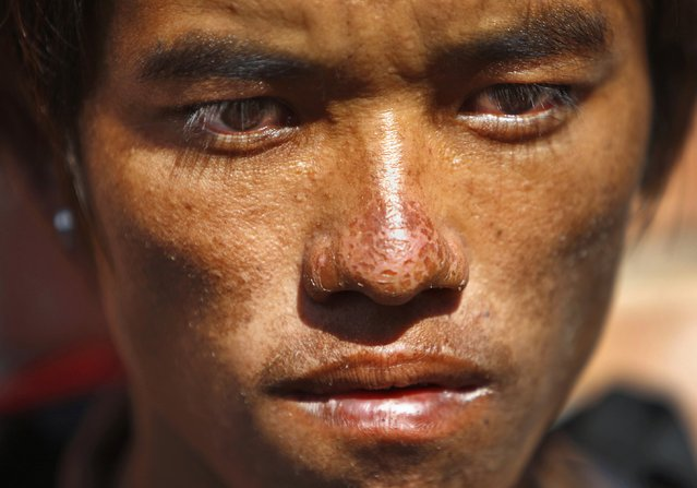 Sete Tamang, 20, avalanche survivor, waits to receive the bodies of his colleagues outside a morgue at Teaching Hospital in Katmandu, Nepal, Monday, October 20, 2014. Nepal was wrapping up rescue operations in its northern mountains Monday, saying all the hikers believed to have been stranded on a trekking route by a series of deadly blizzards are now safe. (Photo by Niranjan Shrestha/AP Photo)