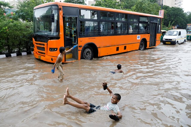Children play on a flooded street after heavy rains in New Delhi, July 21, 2020. (Photo by Adnan Abidi/Reuters)