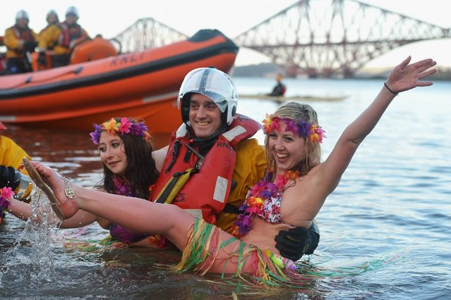 Natalie Tuccia and Sarah Johnston put their arms around a RNLI member as they joined around 1,000 New Year swimmers, many in costume, braved freezing conditions in the River Forth in front of the Forth Rail Bridge during the annual Loony Dook Swim on January 1, 2013 in South Queensferry, Scotland. Thousands of people gathered last night to see in the New Year at Hogmanay celebrations in towns and cities across Scotland..  (Photo by Jeff J. Mitchell)