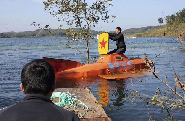Tan Yong (R) prepares to operate his home-made submarine at a lake in Dangjiangkou, Hubei province, October 24, 2014. (Photo by Reuters/Stringer)