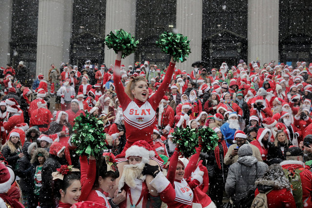 Revellers dressed as Santa Claus and other holiday themed outfits celebrate during the annual SantaCon event in New York City on December 9, 2017. (Photo by Elizabeth Shafiroff/Reuters)