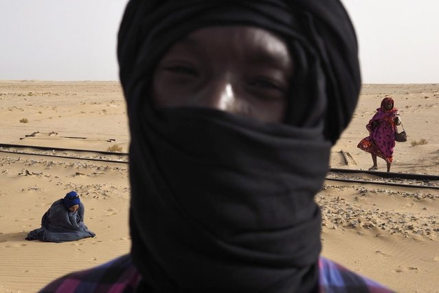 Passengers take a break to pray while travelling on SNIM train carrying iron ore and mine workers across the desert outside Nouadhibou June 25, 2014. (Photo by Joe Penney/Reuters)