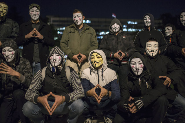 Protesters wearing Guy Fawkes masks pose for a picture in a park in downtown Belgrade November 5, 2014. (Photo by Marko Djurica/Reuters)