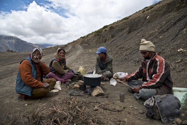 In this August 17, 2016, photo, from left to right, Chhering Chodom, 60, Tashi Yangzom, 50, Lobsang Chhering, 27, and Dorje Tandup, 58, drink milk tea on the side of the road. For centuries, the sleepy valley nestled in the Indian Himalayas remained a hidden Buddhist enclave forbidden to outsiders. Enduring the harsh year-round conditions of the high mountain desert, the people of Spiti Valley lived by a simple communal code – share the Earth's bounty, be hospitable to neighbors, and eschew greed and temptation at all turns. That's all starting to change, for better or worse. Since India began allowing its own citizens as well as outsiders to visit the valley in the early 1990s, tourism and trade have boomed. And the marks of modernization, such as solar panels, asphalt roads and concrete buildings, have begun to appear around some of the villages that dot the remote landscape at altitudes above 4,000 meters (13,000 feet). (Photo by Thomas Cytrynowicz/AP Photo)