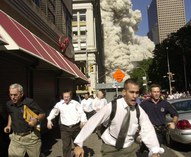 People run from the collapse of World Trade Center Tower  Tuesday, September 11, 2001 in New York. (Photo by Suzanne Plunkett/AP Photo)