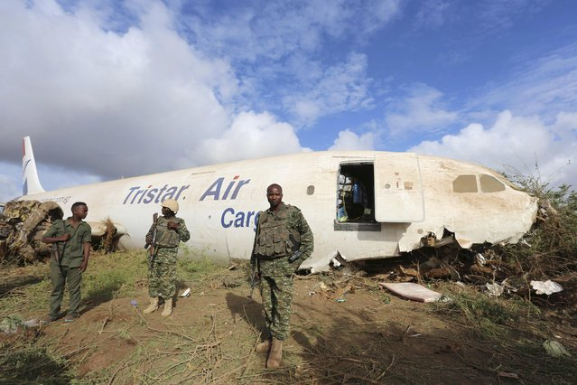 Ugandan soldiers serving in the African Union Mission in Somalia (AMISOM) and a Somalia soldier stand guard as they secure the site where a Tristar Air Airbus A300-200F cargo plane crash-landed in Arbiska outside Somalia's capital Mogadishu, October 13, 2015. (Photo by Feisal Omar/Reuters)