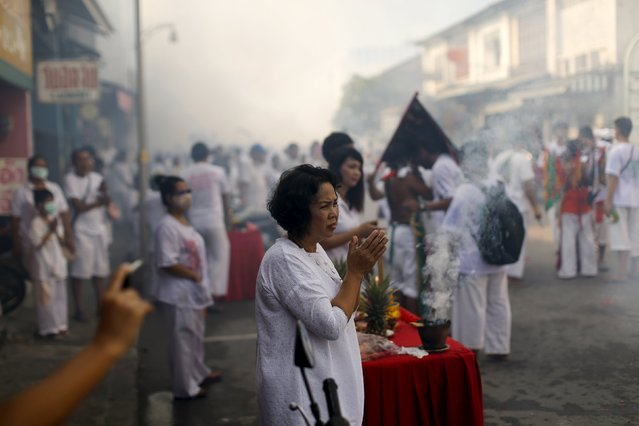 A woman stands outside her house to see devotees of the Chinese Ban Tha Rue shrine procession celebrating the annual vegetarian festival in Phuket, Thailand, October 17, 2015. (Photo by Jorge Silva/Reuters)