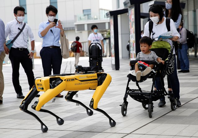 A boy in a stroller reacts to Boston Dynamics' four-legged robot Spot during its demonstration at Tokyo Robot Collection, Japan on September 18, 2020. (Photo by Kim Kyung-Hoon/Reuters)