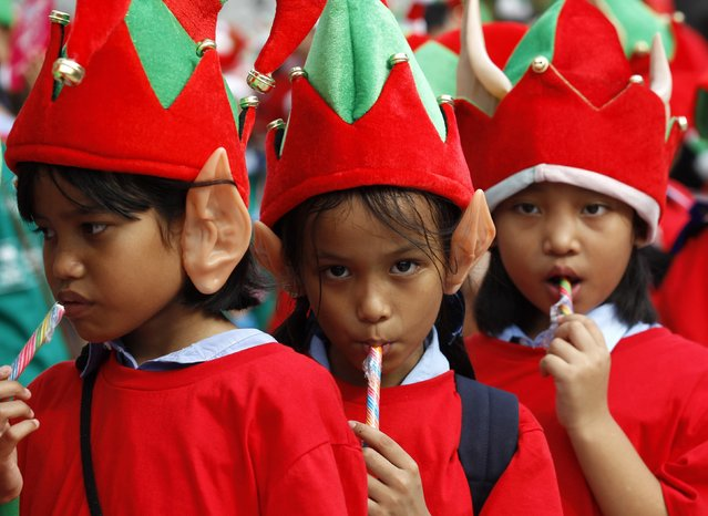 Students gather to break the Guinness World Record for the largest gathering of Christmas elves, outside a shopping mall in central Bangkok, November 25, 2014. (Photo by Chaiwat Subprasom/Reuters)