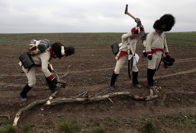 Historical re-enactment enthusiasts dressed as soldiers chop firewood near the southern Moravian village of Herspice November 28, 2014. (Photo by David W. Cerny/Reuters)