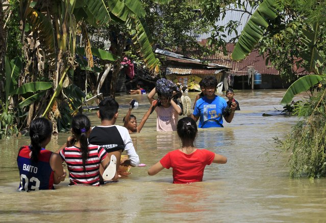 Residents wade across floodwaters after a week typhoon Koppu battered Calumpit town, Bulacan province, north of Manila October 24, 2015. Typhoon Koppu, that dumped heavy rains on the northern Philippines, killing 58 people as it flattened houses and destroyed crops, was petering out on Wednesday, weather officials said. (Photo by Romeo Ranoco/Reuters)