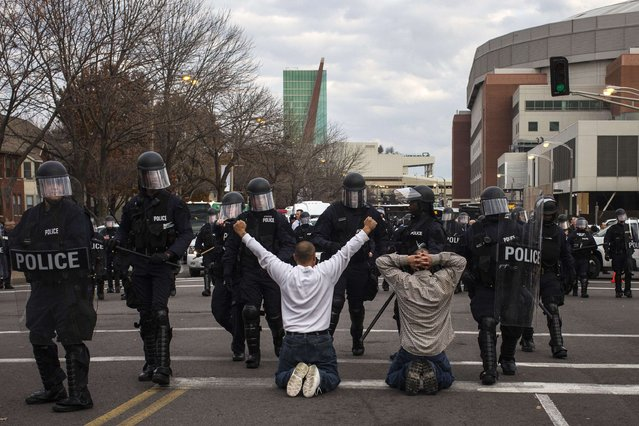 Protesters demanding justice for Michael Brown kneel on the ground before they are detained for disrupting traffic outside the Edward Jones Dome, the site of an NFL football game between the St. Louis Rams and the Oakland Raiders, in downtown St. Louis, Missouri November 30, 2014. (Photo by Adrees Latif/Reuters)