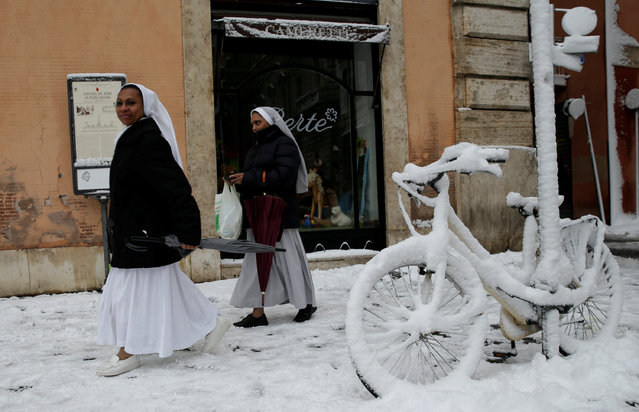 Nuns walk past a bike covered in snow during a heavy snowfall in Rome, Italy on February 26, 2018. (Photo by Max Rossi/Reuters)