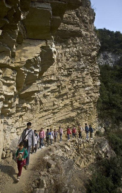 Xu Liangfan, 37, escorts students on a cliff path as they make their way to Banpo Primary School in Guizhou province March 12, 2013. (Photo by Reuters/Stringer)