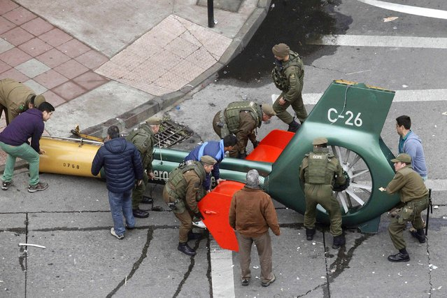 Policemen and rescue workers prepare to lift the wreckage of a police helicopter that crashed on a main avenue in Santiago, November 30, 2014. The helicopter pilot was seriously injured but no person was killed after the helicopter crashed in a street at Chile's capital, police said on Sunday. (Photo by Carlos Vera Alvarado/Reuters)