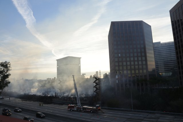 Fire crews work on smoldering hot spots of a large fire that consumed an apartment building that was under construction in Los Angeles, California December 8, 2014. (Photo by Jonathan Alcorn/Reuters)