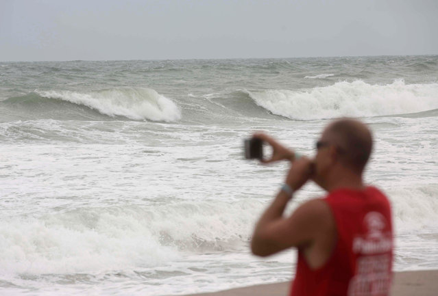 A man takes pictures of the waves while Hurricane Matthew approaches in Melbourne, Florida, U.S. October 6, 2016. (Photo by Henry Romero/Reuters)
