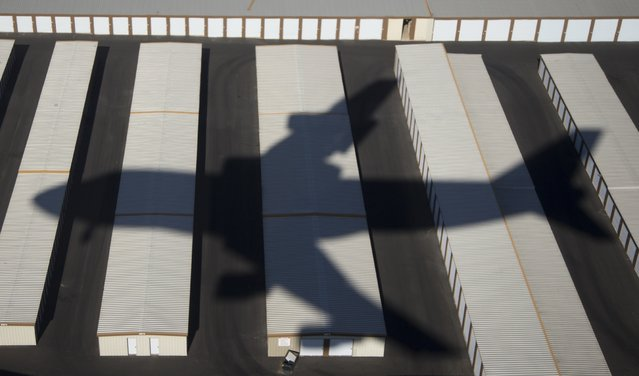 A shadow is cast by Air Force One, with President Barack Obama aboard, as it approaches McCarran International Airport in Las Vegas, Friday, November 21, 2014, as the president travels to Del Sol High School to speaks about the steps he will be taking on immigration. (Phhoto by Carolyn Kaster/AP Photo)