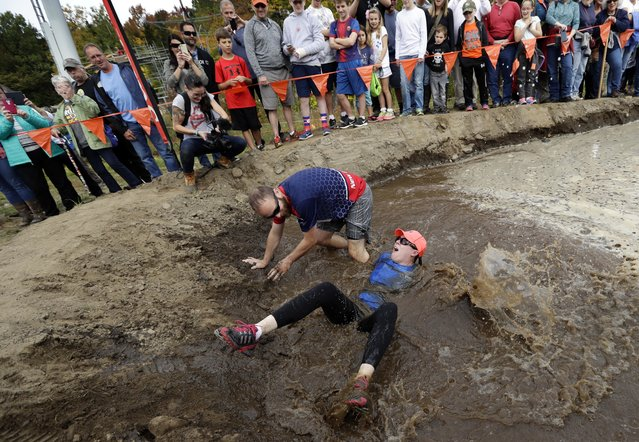 Robin Gahan gets dumped into the mud pit after her husband, Steven Gahan, of Rochester, N.Y., lost his balance during the North American Wife Carrying Championship, Saturday, October 8, 2016, at the Sunday River Ski Resort in Newry, Maine. (Photo by Robert F. Bukaty/AP Photo)