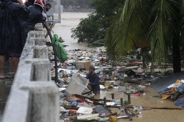 A resident tries to save belongings as floods continue to rise in Marikina, Philippines due to Typhoon Vamco on Thursday, November 12, 2020. (Photo by Aaron Favila/AP Photo)