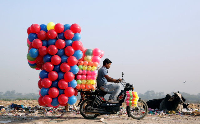 A man carries children's coloured plastic balls on his motorcycle in Delhi, India, March 20, 2018. (Photo by Cathal McNaughton/Reuters)