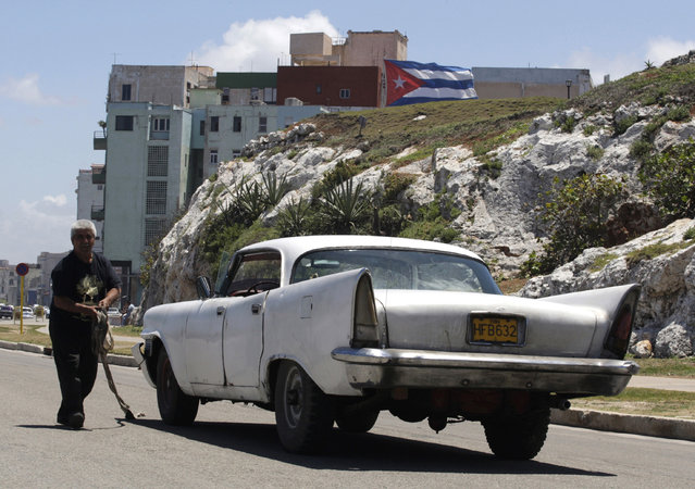 A man repairs his 1958 Chrysler car on a street in Havana, April 13, 2010. (Photo by Enrique De La Osa/Reuters)