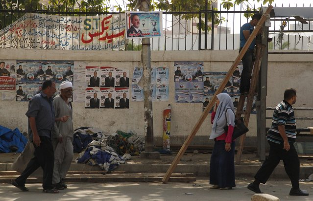 People walk past electoral banners on a wall on a street  in Alexandria, Egypt, October 18, 2015. (Photo by Asmaa Waguih/Reuters)