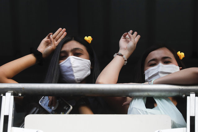 Two women flash three-finger protest gestures while wearing headbands adorned with yellow ducks, which have become a good-humored symbol of resistance during anti-government rallies, Friday, November 27, 2020 in Bangkok, Thailand. (Photo by WasonWanichakorn/AP Photo)