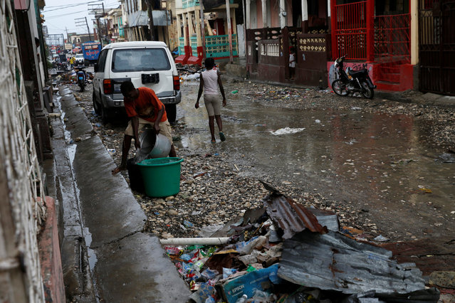 A man collects rain water in a plastic container on the street, after Hurricane Matthew hit Jeremie, Haiti, October 16, 2016. (Photo by Carlos Garcia Rawlins/Reuters)