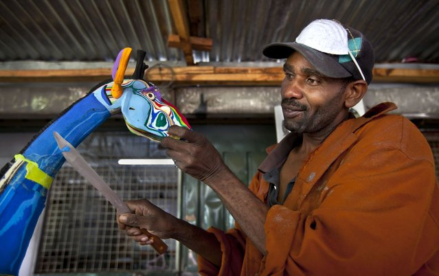 In this photo taken Monday, April 29, 2013, Jackson Mbatha, 40, uses a knife to carve part of the neck of a large giraffe he is making from pieces of discarded flip-flops, at the Ocean Sole flip-flop recycling company in Nairobi, Kenya. The company is cleaning the East African country's beaches of used, washed-up flip-flops and the dirty pieces of rubber that were once cruising the Indian Ocean's currents are now being turned into colorful handmade giraffes, elephants and other toy animals. (Photo by Ben Curtis/AP Photo)