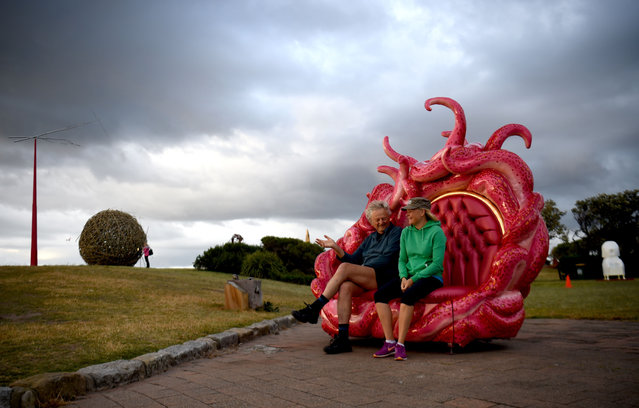 """Visitors sit on a sculptures on display between Bondi Beach and Tamarama Beach on the first day of the """"Sculpture by the Sea"""" exhibition in Sydney on October 20, 2016. Celebrating it's 20th anniversary, Sculpture by the Sea is the world's largest annual, free-to-the-public, outdoor sculpture exhibition. (Photo by Peter Parks/AFP Photo)"""