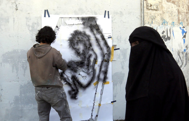 A picture made available on 21 October 2016 shows a Yemeni artist spraying a graffiti on a wall in protest against the ongoing conflict and the worsening economic situation in the war-affected country, in Sana'a, Yemen, 20 October 2016. According to reports, since March 2015, ongoing conflict and the Saudi-led airstrike campaign in Yemen have left 21.2 million – 82 percent of Yemen's population – in dire need of humanitarian aid, including 9.9 million children. (Photo by Yahya Arhab/EPA)