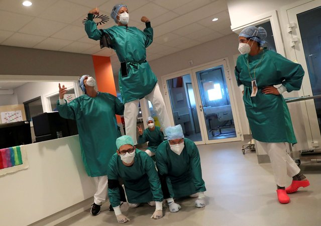 Healthcare workers wearing face masks, gloves and overall suits form a human pyramid to relax in the coronavirus disease (COVID-19) intensive care unit at the MontLegia CHC Hospital in Liege, Belgium, May 15, 2020. (Photo by Yves Herman/Reuters)