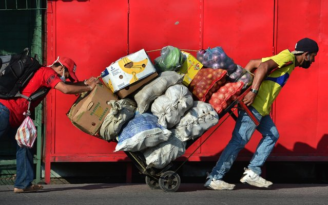 Two men carry a cart loaded with fresh goods at a street in Tegucigalpa on June 8, 2020, after the governmet announced the resumption of economic activity, amid the COVID-19 pandemic. Honduras reopens its business activities, cautiously, after almost three months of confinement, though, according to experts, at the worst time to do so due to the rapid rise of the coronavirus and at high risk of closing again. (Photo by Orlando Sierra/AFP Photo)