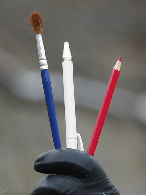 A woman holds a brush, a pen and a pencil in the colours of the French flag during a tribute for the victims of the shootings at the satirical weekly newspaper Charlie Hebdo and a Jewish deli in Paris, in Ottawa January 11, 2015. (Photo by Chris Wattie/Reuters)