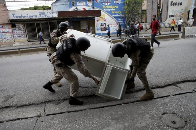 National Police officers pick up a refrigerator from the ground during a demonstration against the results of the presidential elections in Port-au-Prince, Haiti, November 26, 2015. (Photo by Andres Martinez Casares/Reuters)