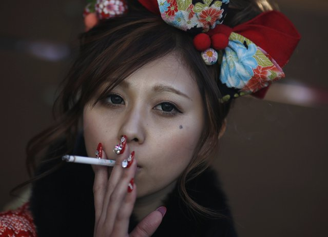 Juri Mitomi, 20, holds a cigarette after a Coming of Age Day celebration ceremony at an amusement park in Tokyo January 12, 2015. According to a government announcement, more than 1.2 million men and women who were born in 1994 marked the coming of age this year, an increase of approximately 50,000 from last year. The increase is also the first since 1995. (Photo by Yuya Shino/Reuters)