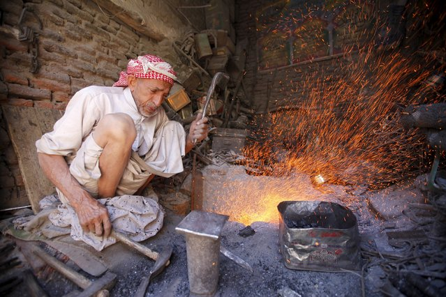A man works in his shop at a market place in the old quarter in the Yemeni capital Sanaa, December 3, 2015. (Photo by Mohamed al-Sayaghi/Reuters)